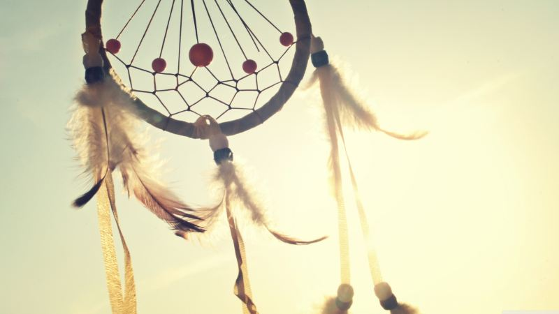 A small dream catcher with red beads, and white feathers with brown tips blows in the wind, backlit by the sun.
