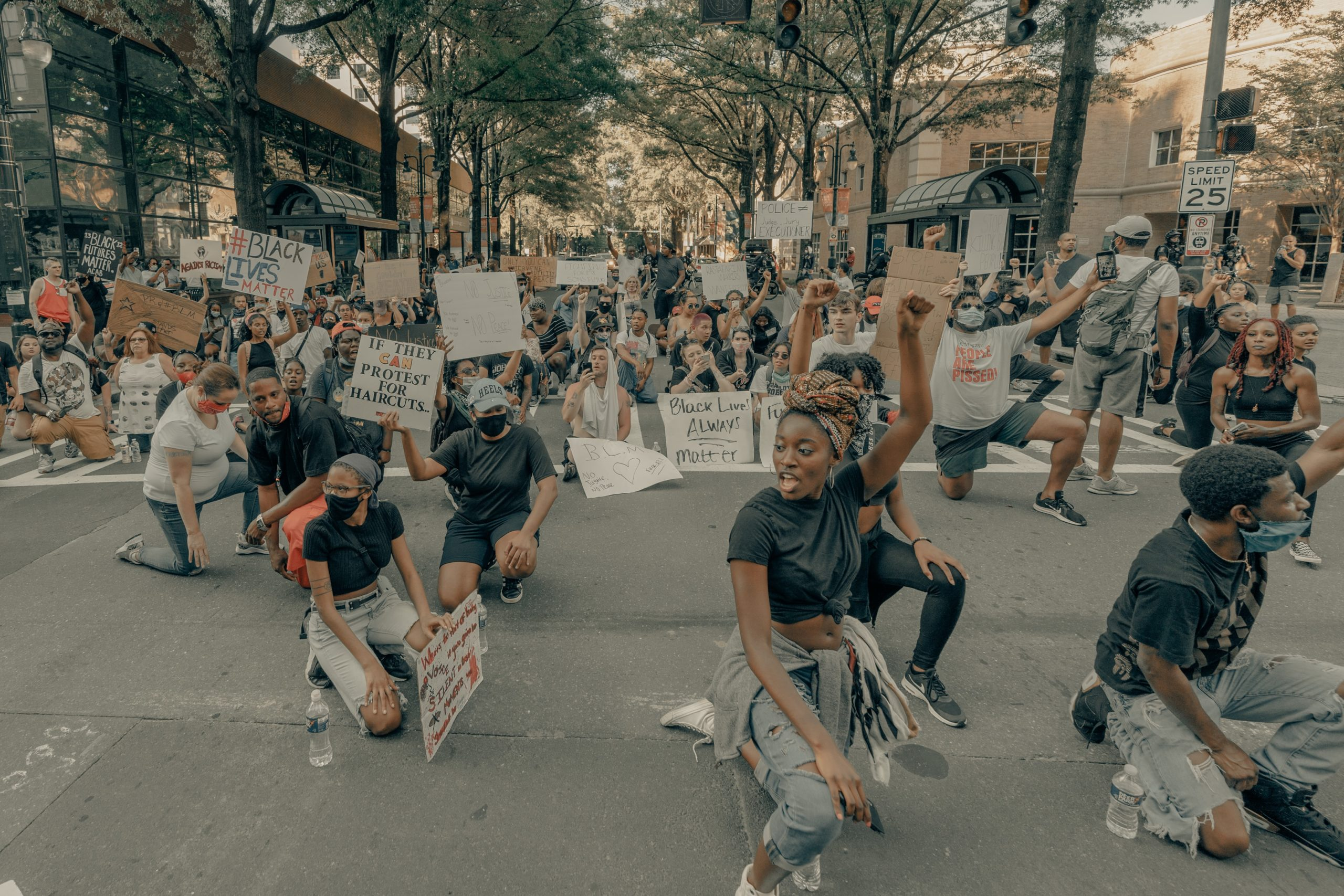 Photo from the George Floyd protests in Uptown Charlotte: Many people of color wearing black T-shirts and tattered jeans are kneeling on one knee in a public intersection holding signs & their fists raised. Behind them are hundreds of people sitting in the street with their own protest signs.