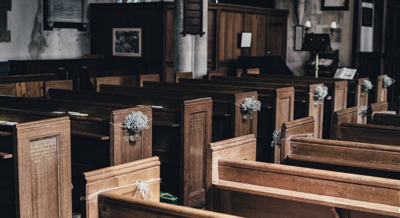 Rows of old wooden church pews with straight backs, no padding, stained dark brown. They are decorated with small bunches of white flowers but even the flowers look grungy and old.