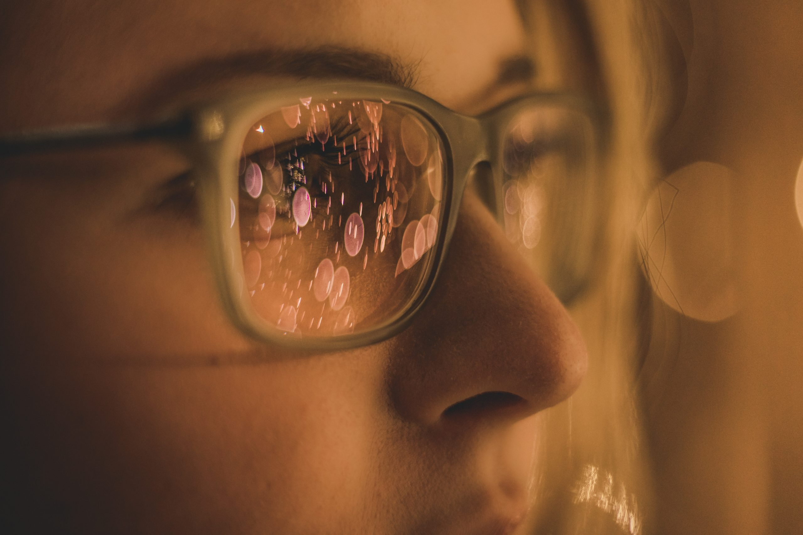 Close up of a blonde woman wearing black and beige plastic rimmed glasses. Many balls of pink light are reflected in the lenses, so her eyes are almost entirely obscured from view.