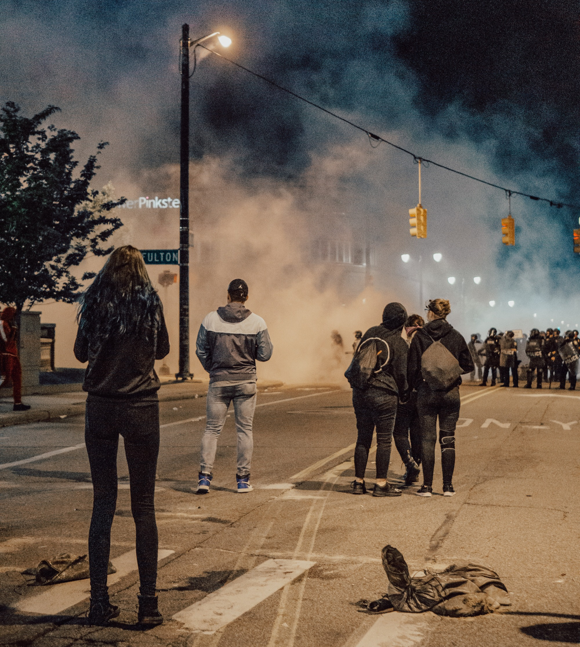A Justice ForGeorge Floyd protest in Grand Rapids, MI: The city street is completely empty except for a handful of protestors standing in the road and some disgarded clothing on the ground. The air is thick with tear gas so that you can