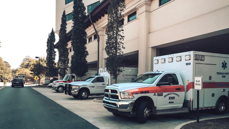 a series of ambulances are parked in the garage of a large white hospital.