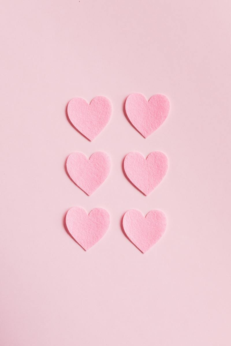 On a pale pink background, six pink hearts have been cut out of felt and arranged in two columns of three next to each other.