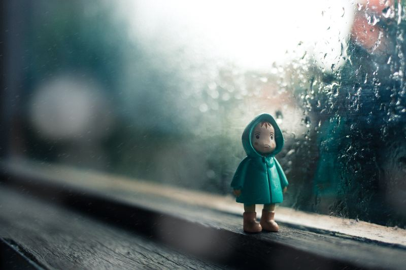 A tiny figurine of a child in a turquoise rain coat stands on a window sill in front of a rainy and gloomy window.