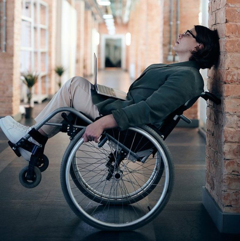 A light skinned woman with brown short hair and black glasses leans her wheelchair backward so her had is leaned against a brick wall. Her eyes are closed and she looks tired and frustrated.