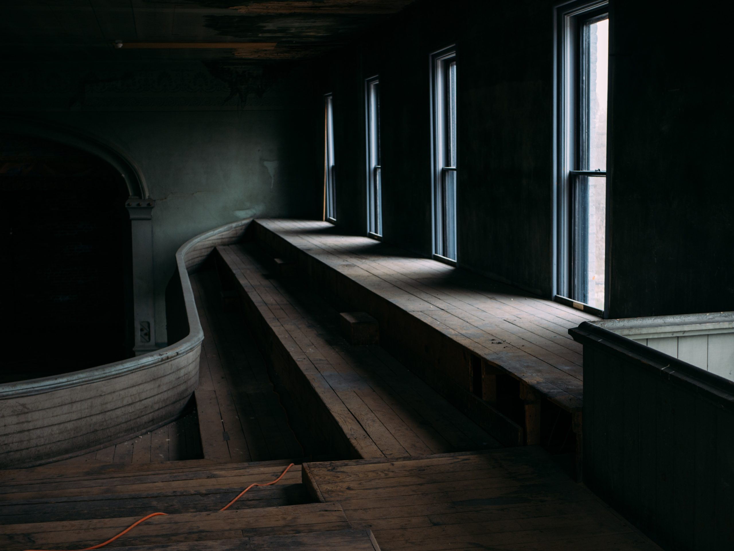 A dusty, dimly lit room filled with empty space and rough wooden floor boards. Along one wall there is a series of narrow windows, that let in very little light.