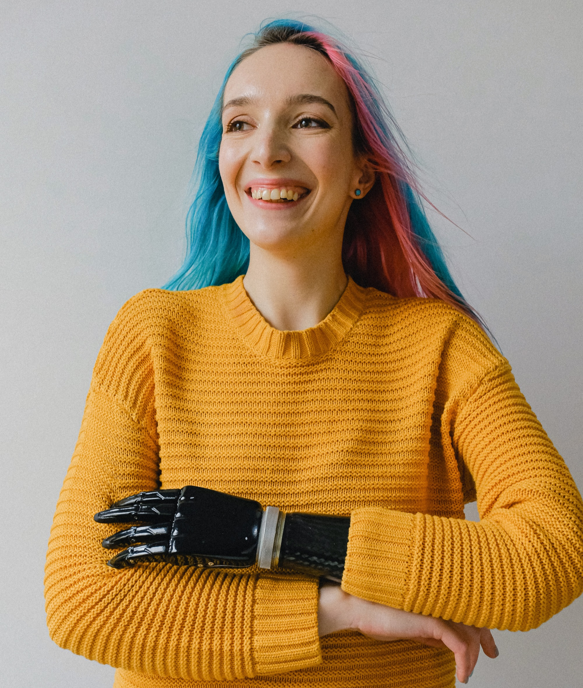 A light skinned woman with long pastel rainbow hair and a golden yellow sweater is smiling widely while looking off to the left of the camera. She holds her arms in front of her and it