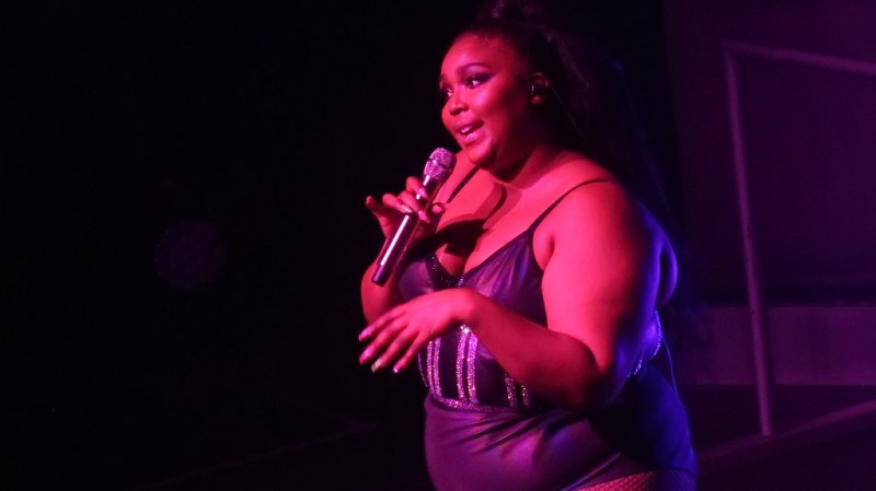 Lizzo, a large black woman, is lit by red light, She's wearing a black leotard with glittery stripes, her hair is pulled back, and she sings into a microphone while showing some attitude with her body language.