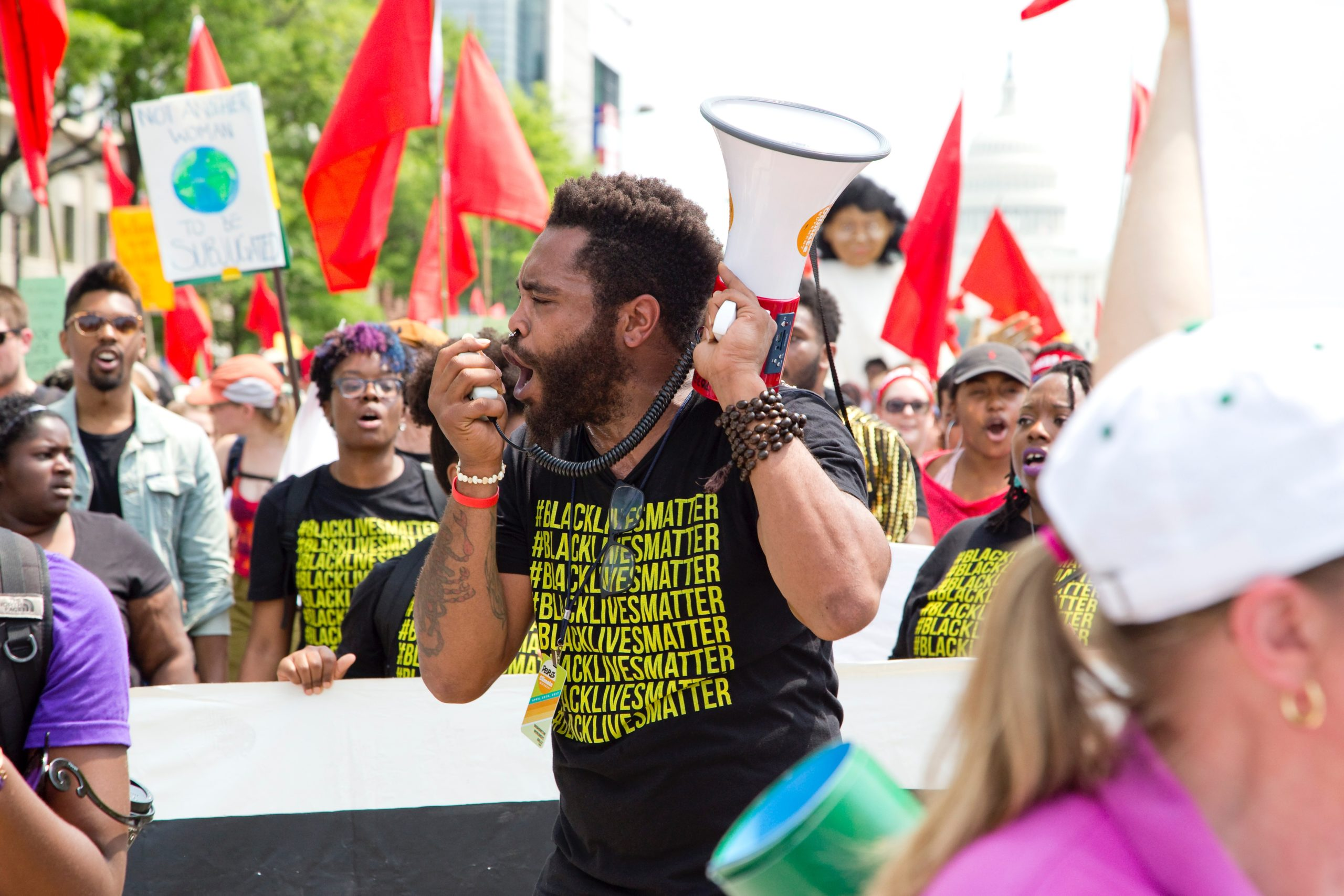 A man of color wearing a black lives matter t-shirt talks passionately into a megaphone, surrounded by other excited protestors.