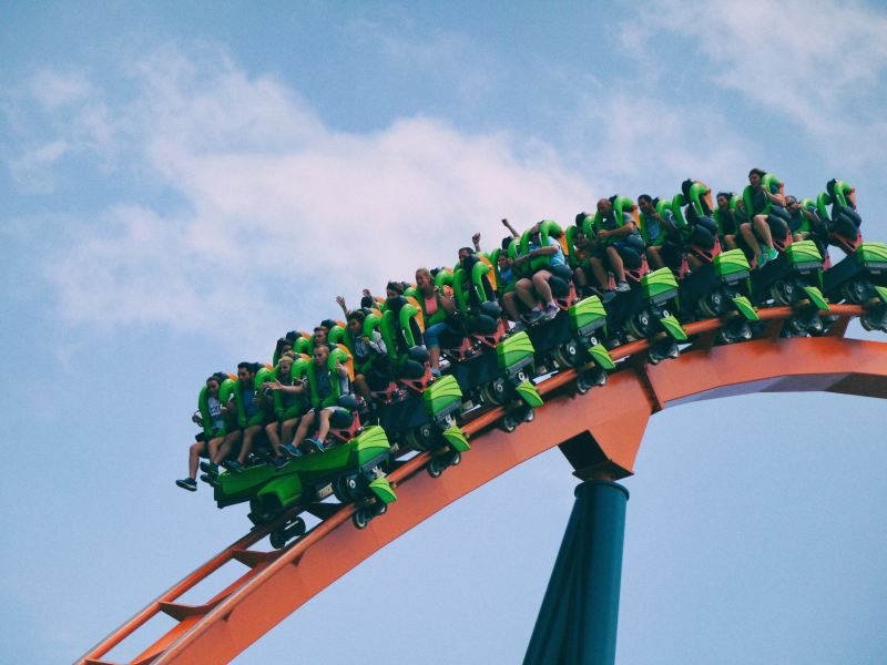 An open faced set of cars on green and orange roller coaster makes its way down a steep decline, so that it looks like the people in it are about to fall out.