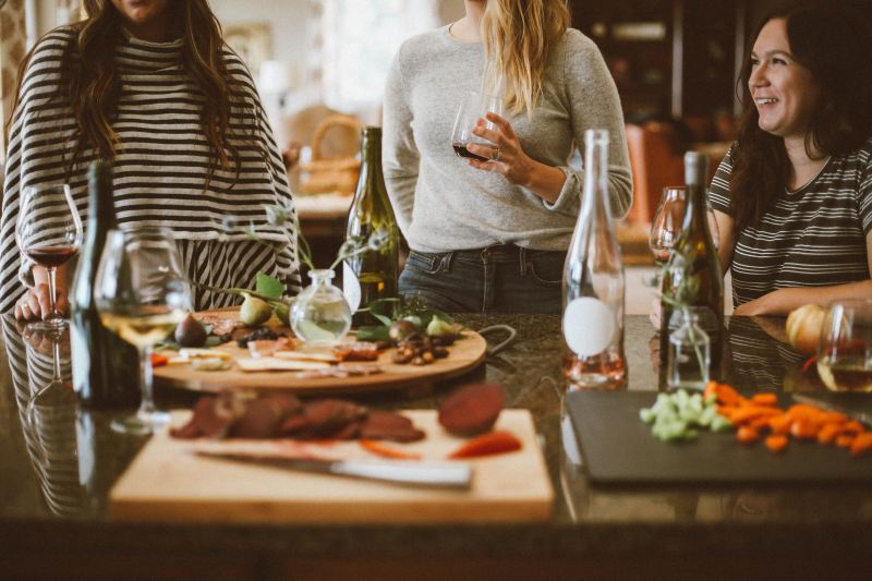 Three women spend time together, gathered around a table covered in food and bottles of wine.