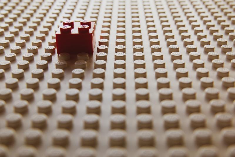 A large flat beige lego board with a single square red lego attached to it.