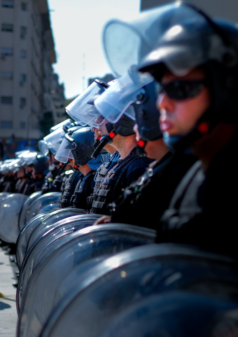 A closeup of an unbroken line of police wearing riot gear and holding shields.