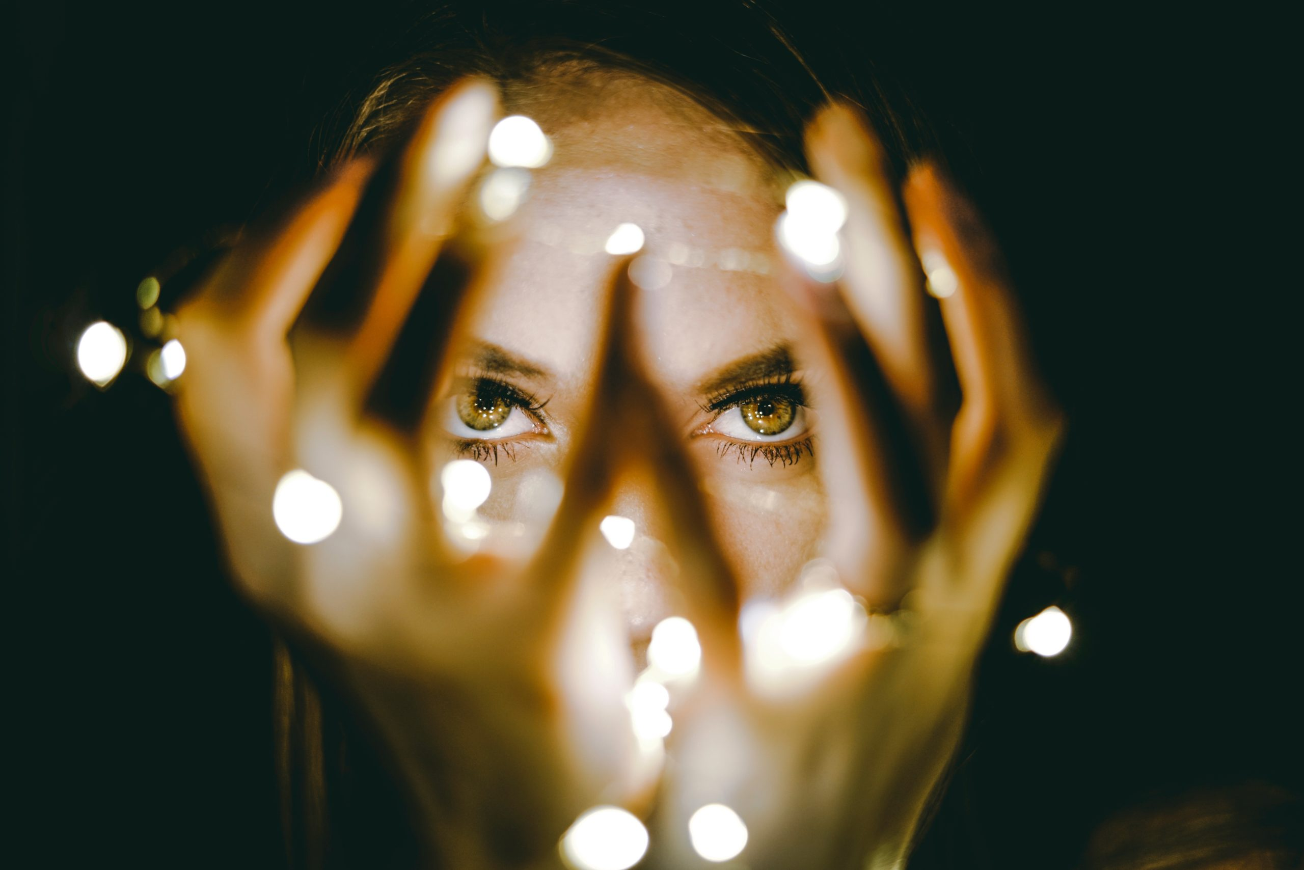 A woman's face and brown eyes are lit only by a string of twinkle lights held in her hands in front of her.