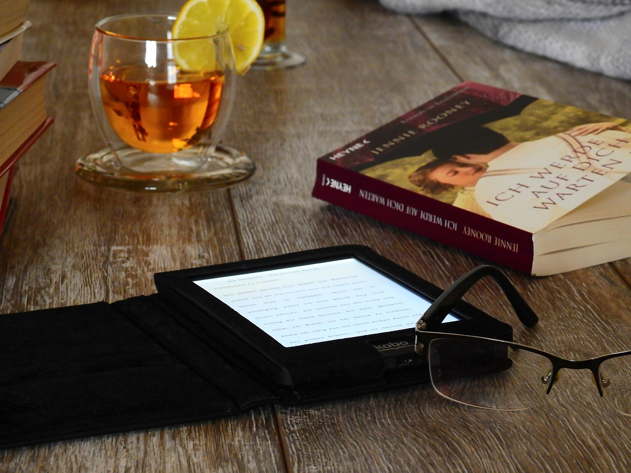 A table where someone is enjoying a cold drink, a paperback book, and an E-Reader