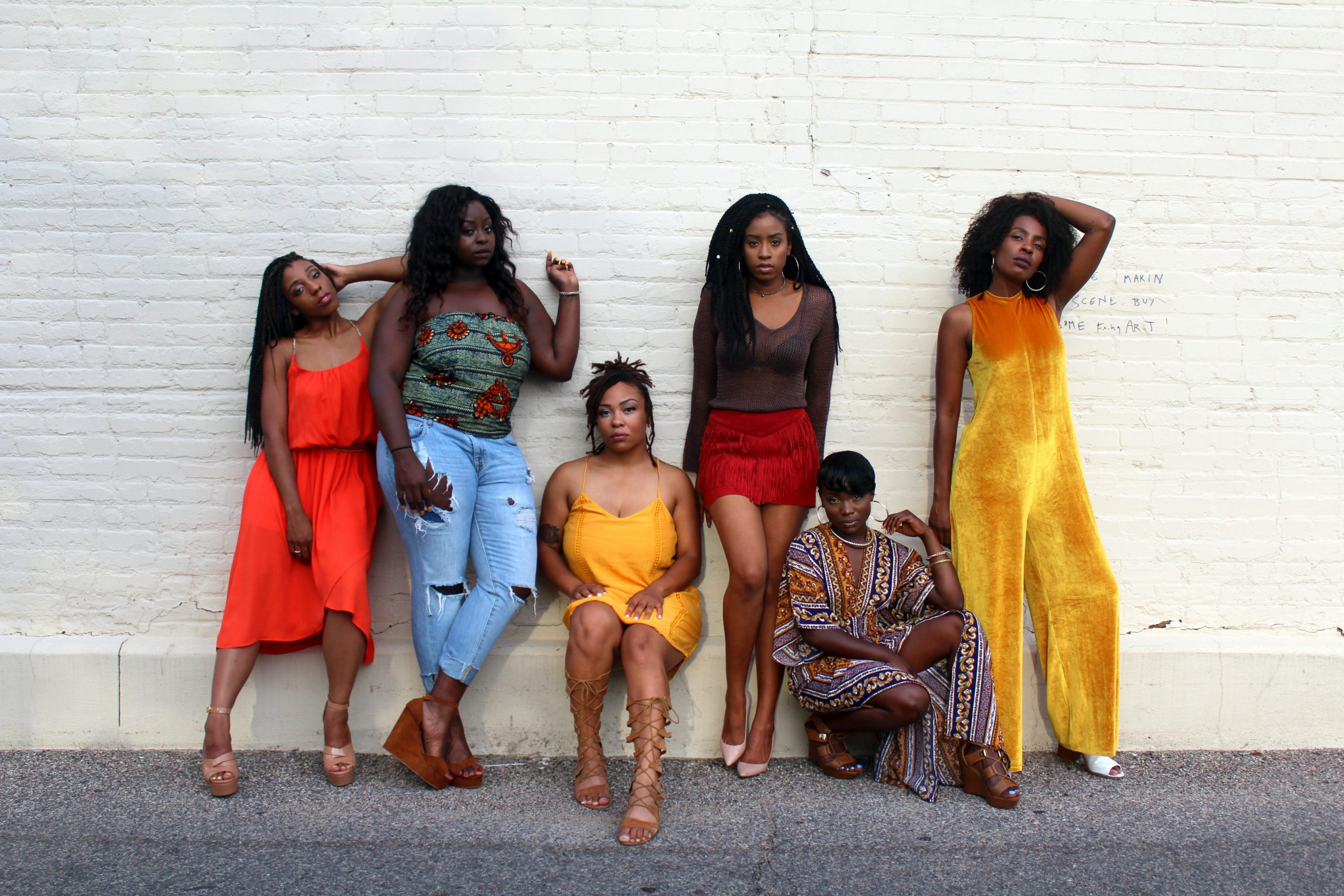 Six Black women looking good as hell, posing against a painted white brick wall. From left to right, a woman wears an orange calf length dress and has her head cocked to the left and leans her elbow against the next woman. She is tall and thick in tattered blue jeans and pale green tube top, her left hand is backed against the wall and she doesn