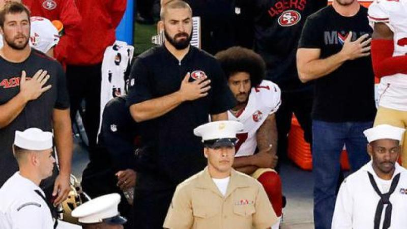 Colin Kaepernick, looking serious, kneels during the national anthem in order to protest police brutality against people of color, while he is surrounded by other men who are standing.