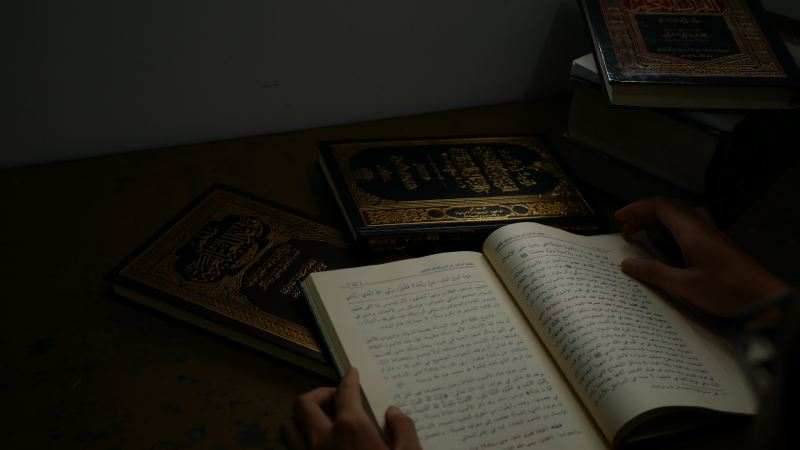 In a very dim room, a person holds open a quran, surrounded by other similar manuscripts with dark green or grown leather and ornate gold inscriptions.