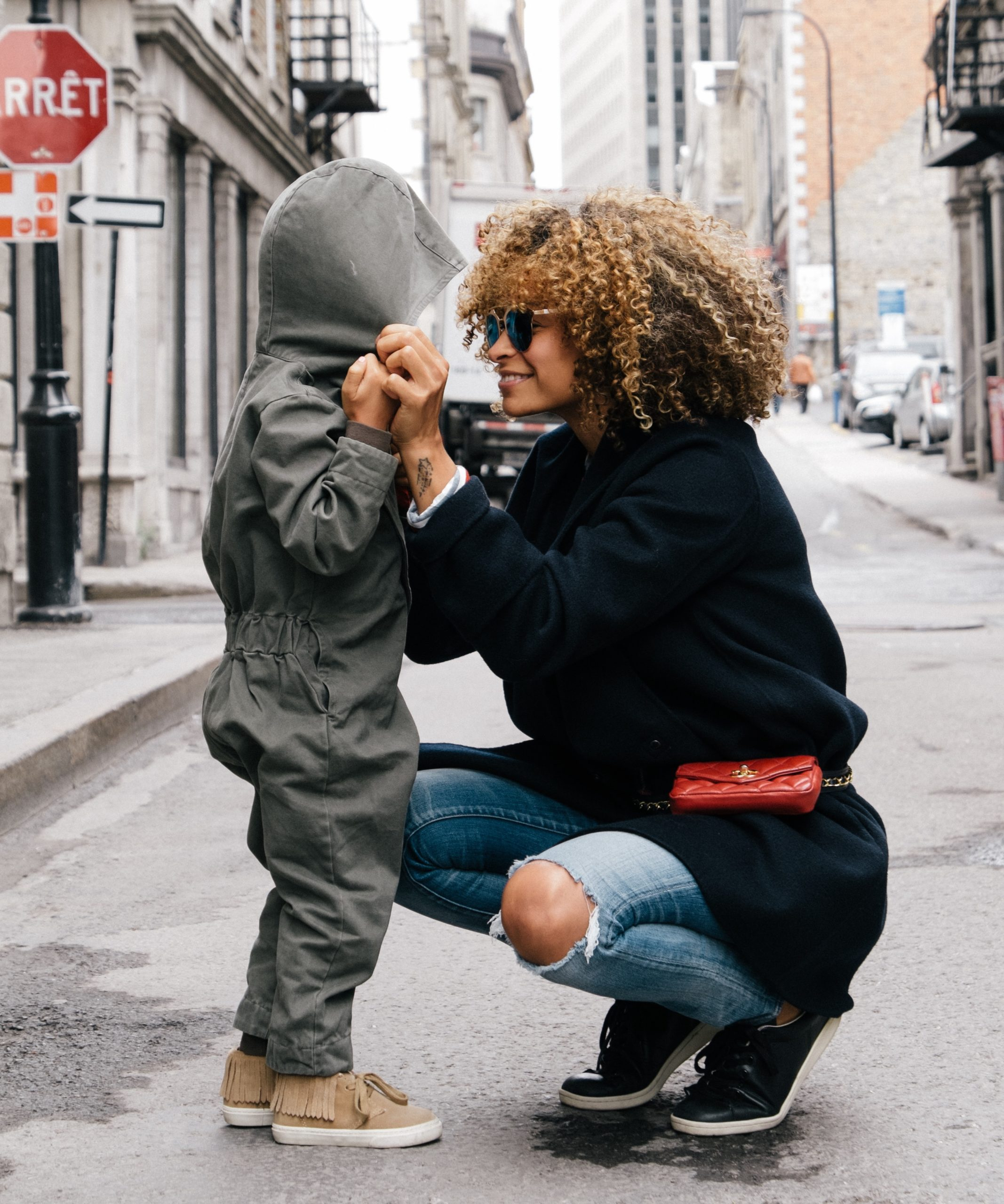 A young woman of color with natural hair and sunglasses grins as she squats next to her child, looking into his eyes warmly.