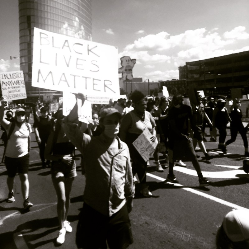 "A black and white photo of Nashville, TN BLM protests with an overexposed filter on it. Many people walk through the center of the street holding signs, wearing masks. Closest to the camera is a person holding a white sign that just says ""Black Lives Matter"" in all caps."