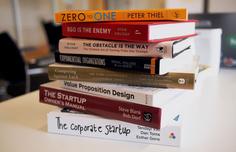 A stack of multi colored books on entrepreneurial advice: Zero to One, Ego is the Enemy, The Obstacle is the Way, Exponential Organizations, Competing Against Luck, Value Proposition Design, The Starup Owner's Manual, and The Corporate Startup.