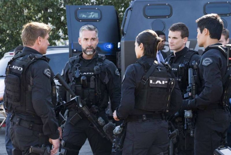 A video still from the TV show SWAT: Five of the characters dressed in riot gear but at ease gather in a circle to discuss their next movements.