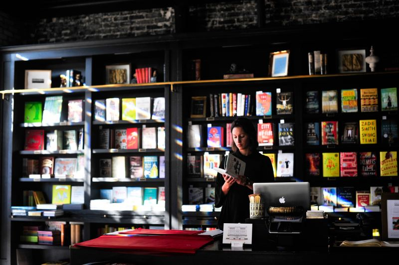 A woman stands behind the counter of a bookstore, the wall behind her lined with many colored books in a black book case.