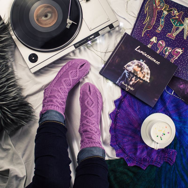 "A person sits on their bed, surrounded by their self care kit: a grey fuzzy pillow, purple knitted socks, a record player playing music, the photography book ""Luminescence"" by Brandon Woelfel, a colorful print of ""Prince 1999,"" hot chocolate with whipped cream and sprinkles, and a deep blue and purple knitted scarf."