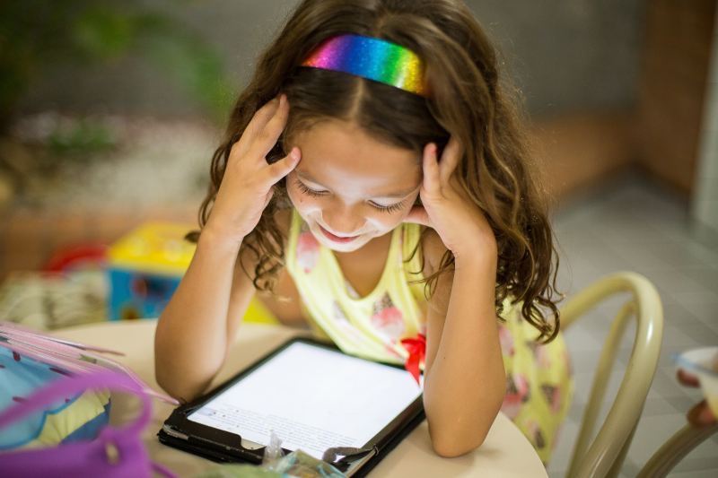 A little girl wearing a yellow dress and rainbow headband reads happily from her tablet
