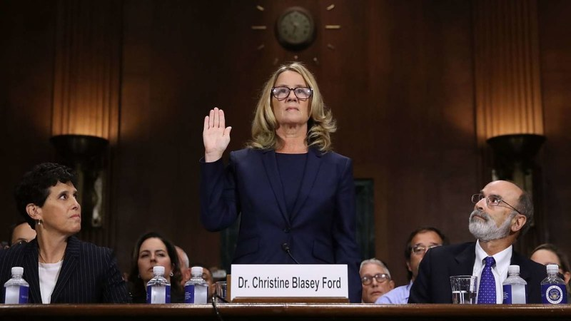 A photo of Dr. Christine Blasey Ford at her hearing regarding her accusations against Kavanaugh. She is standing with her hand up as if she's being sworn in, and perfectly symmetrical on either side of her, there is a woman and a man sitting to either side looking at her intensely.