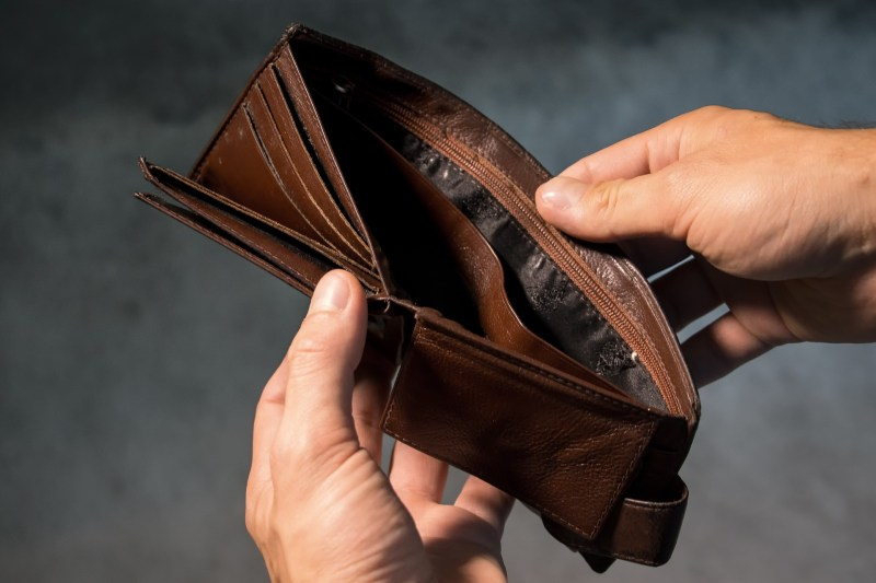 A person pulls the sides of their wallet open, revealing that it's completely empty.