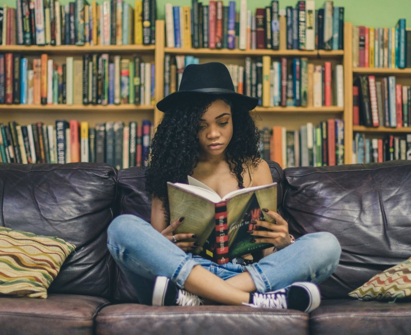 A woman with light brown skin and black tightly coiled hair sits on a leather couch, her legs crossed, reading a book. She is wearing blue jeans, sneakers, a flesh colored tank top, and a black fedora style hat. There are three full bookshelves behind her.