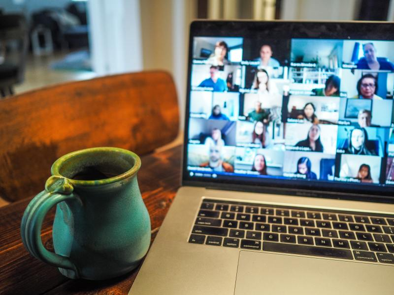 A silver laptop with black keys with a full screen of 15+ people in a zoom call. The laptop is on a reddish brown wooden table and a turquoise pottery mug sits next to it.