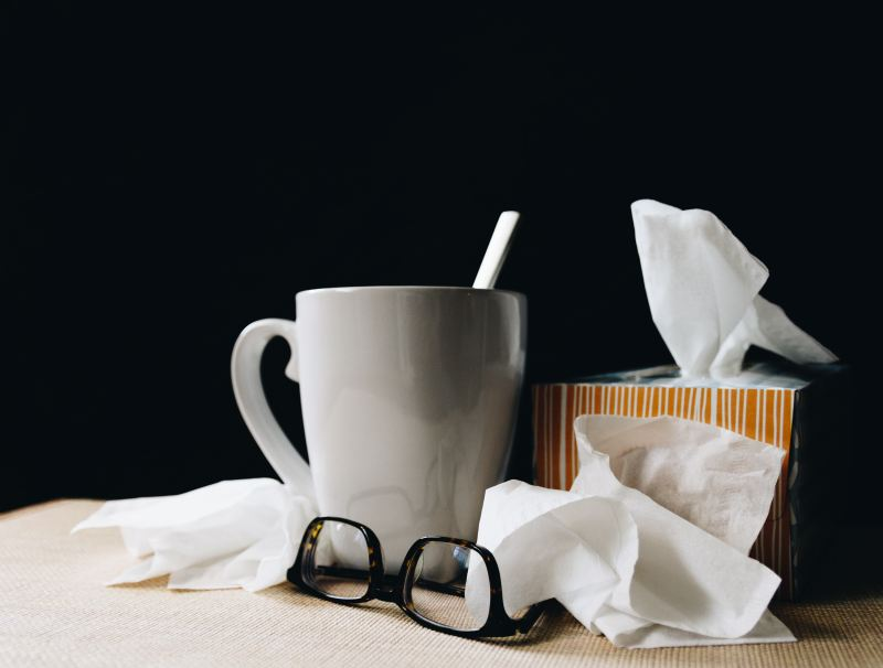 A table is loaded with a white mug of tea, an orange box of kleenex, a brown pair of glasses, and many stray tissues around.