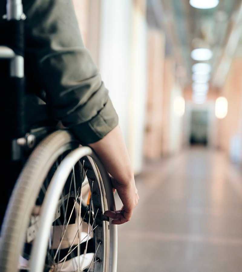 A long view of a hallway in the distance as if you are seeing it from the perspective of the person in a wheelchair that's close to the camera, of which you can only see their right wheel and arm.