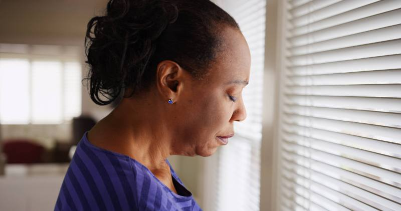 A middle aged black woman with her hair pulled back is wearing a purple striped shirt and dark blue stud jewel earring. She faces her window, the white blinds are closed, and her eyes are closed, as if she's filled with a deep heavy sorrow.