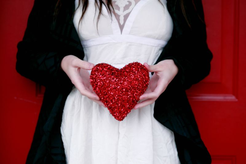 A woman wearing a white dress and black jacket stands in front of a red wall, holding a bright red sparkly heart between her hands approximately where her uterus would be.