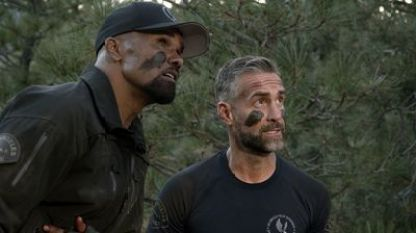A video still from the TV show SWAT: Two leading characters hide in some pine trees, wearing black, with black smudges on their faces.