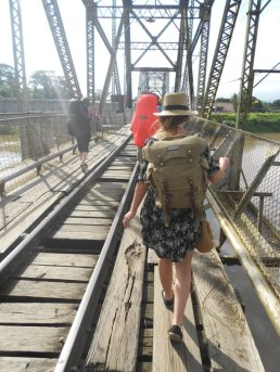 A woman walks across a large wooden bridge with railroad tracks next to her, metal beams above, and muddy water beneath. She's wearing a blue summer dress, a straw hat, and a large olive colored backpack. She is facing away from the camera.