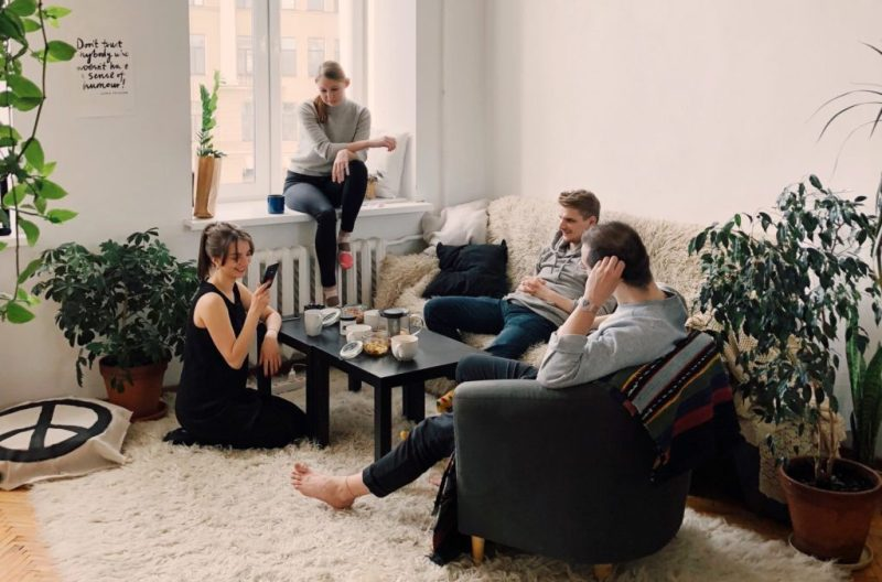 Four friends sit casually around a coffee table in their mostly off white living room. One sits on the window sill, another kneels on the floor looking at her phone, and two others sit on the couch and arm chair.