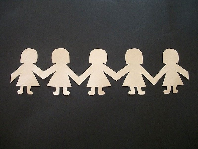 On a black background, a light beige paper cutout of a chain of people wearing skirts and with bobbled haircuts.