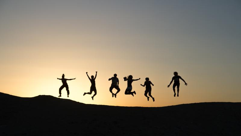 A wide shot of a horizon, the sun almost set, and black silhouettes of six people jumping into the air with enthusiasm.