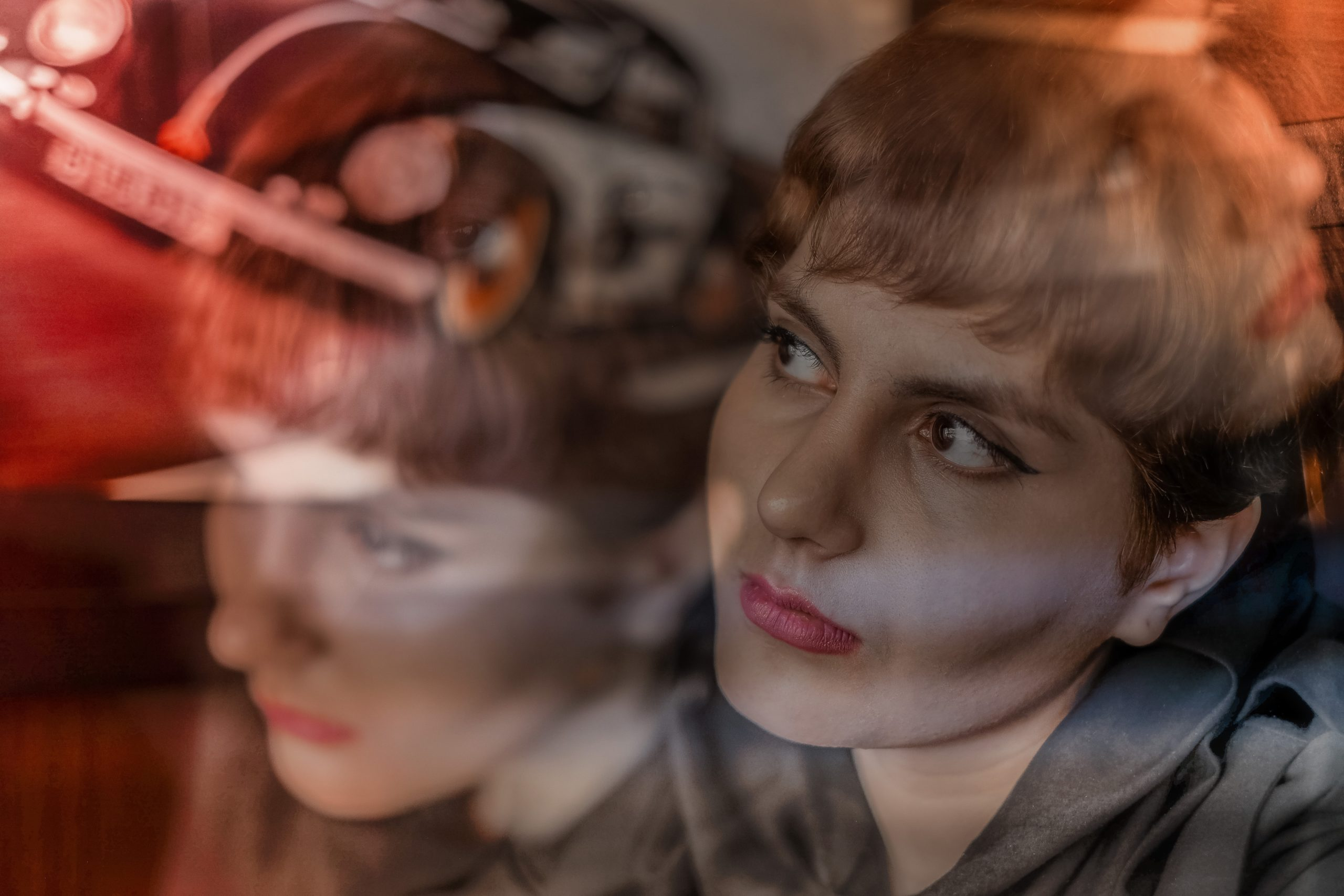 A photo taken with multiple exposures so that a woman's face appears in several different positions and expressions, overlapping one another, with additional colors and light sources mixed in. She is light skinned with very short hair, a grey blouse, and pink lipstick.