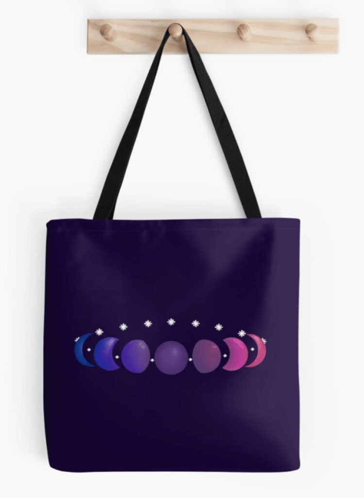 A ring made of white stars and the phases of the moon. The moons are colored in a textured gradient with the colors of the bisexual pride flag. The design is demoed on a dark purple tote bag with a black strap.