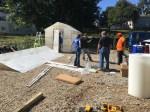 Columbia Gas volunteers assembling donated greenhouses