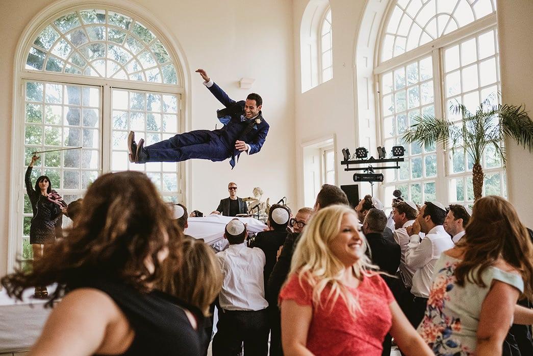 Kew Gardens jewish dancing. Groom lifted high into air.
