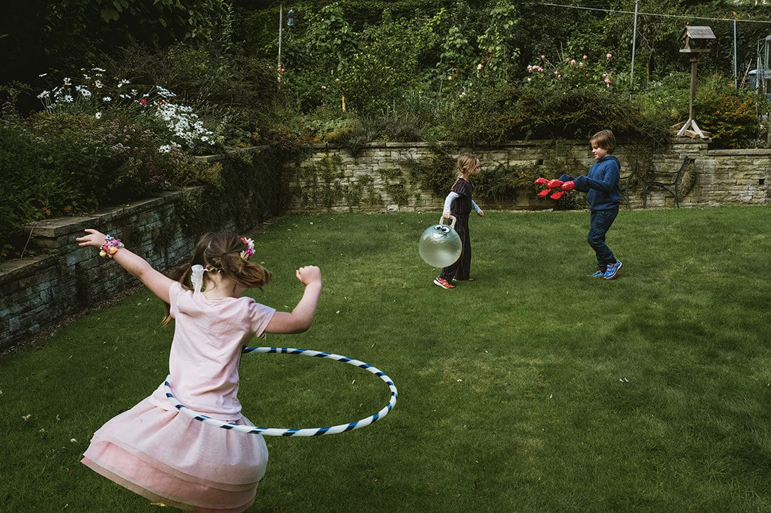 family portrait photography captured in a family garden - young girl in pink dress spins a hula hoop in the foreground, whilst in the background another girl holds a spacehopper as her brother approaches her with lobster claw toys replacing his hands