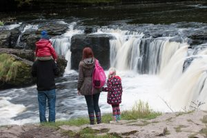 Family standing in front of a waterfall in Aysgarth