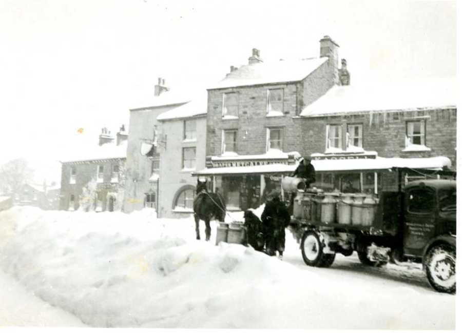 Hauling milk cans by sledge to the milk lorry in Hawes during the winter of 1947. Collection of Dales Countryside Museum