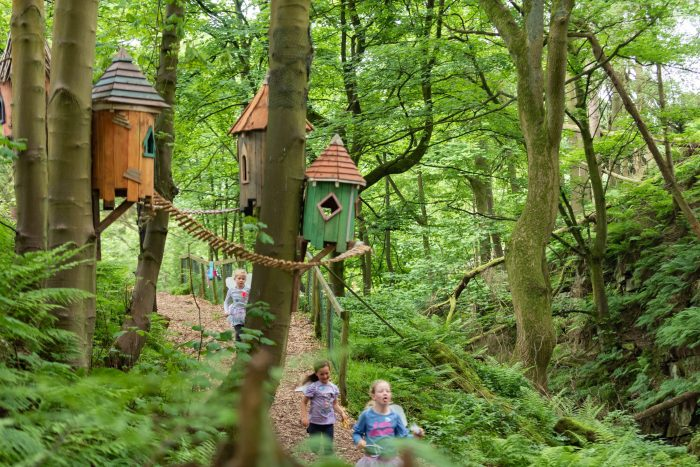 Children run through forest. Fairy houses hung from the trees